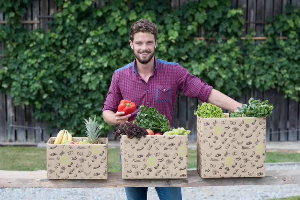 Sie sehen: Junges Gemüse und davor drei Kisten vom BioFerdl